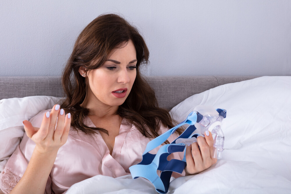 woman is extremely frustrated about how she has to use a cpap in bed to sleep because of her sleep apnea - Learn About Two of My Patients Who Were Affected by Sleep Apnea and Retired Their CPAP Machines